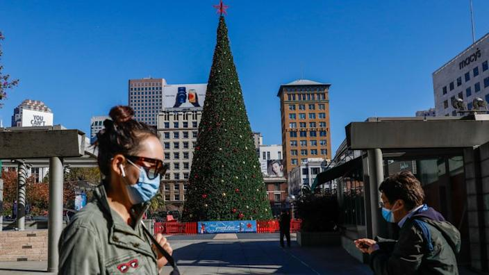 People walk through a quiet Union Square, past a Christmas tree, in San Francisco, California on 1 December 2020