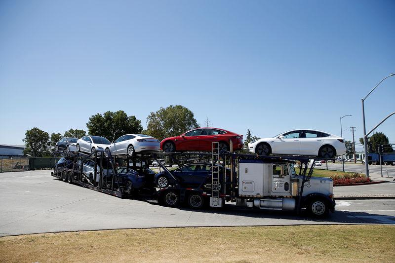 FILE PHOTO: A car carrier trailer carries Tesla Model 3 electric sedans, is seen outside the Tesla factory in Fremont