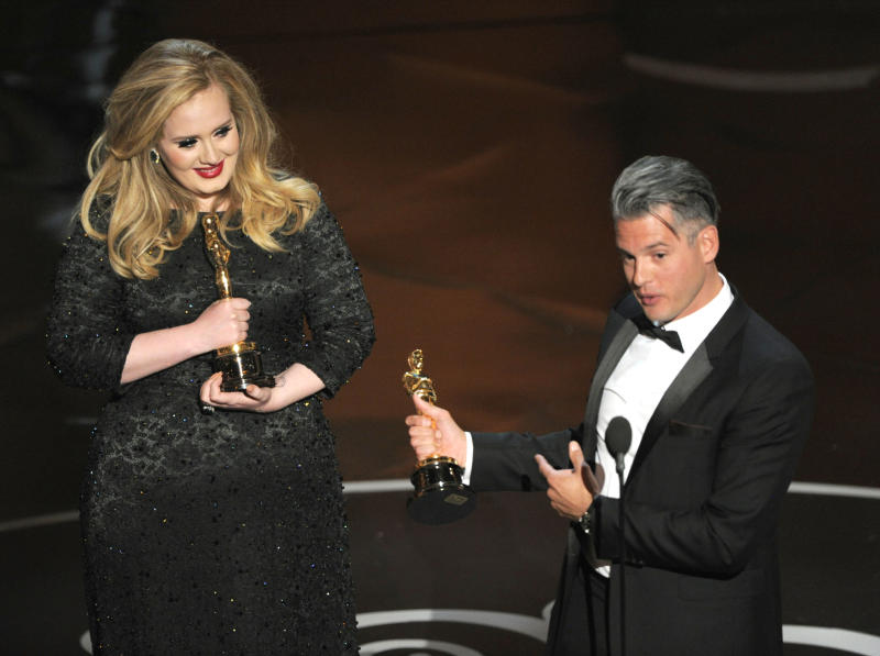 """Singer Adele, left, and musician/producer Paul Epworth accept the award for best original song for """"Skyfall"""" from """"Skyfall"""" during the Oscars at the Dolby Theatre on Sunday Feb. 24, 2013, in Los Angeles. (Photo by Chris Pizzello/Invision/AP)"""