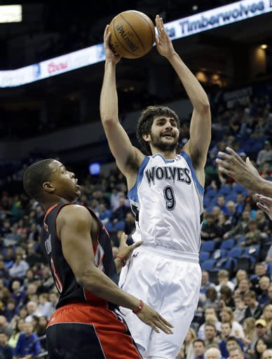 Minnesota Timberwolves' Ricky Rubio, right, of Spain, lays up a shot past Toronto Raptors' Kyle Lowry in the first quarter of an NBA basketball game ,Friday, April 5, 2013, in Minneapolis. (AP Photo/Jim Mone)