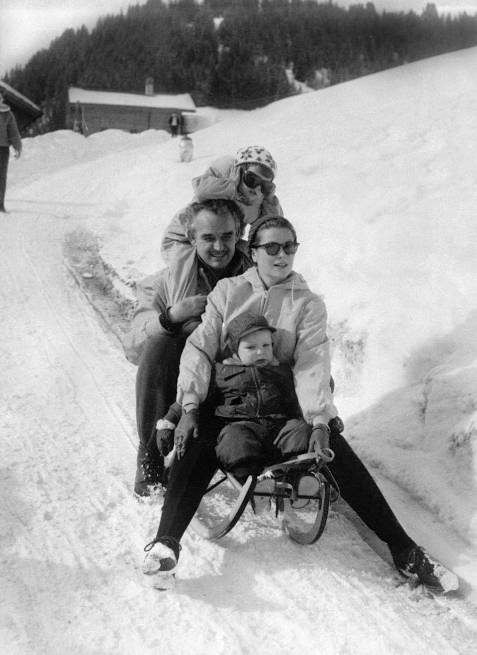 <p>Prince Rainier and Princess Grace of Monaco and their children Caroline and Albert slide down a road in Switzerland during winter vacation, circa 1960.</p>