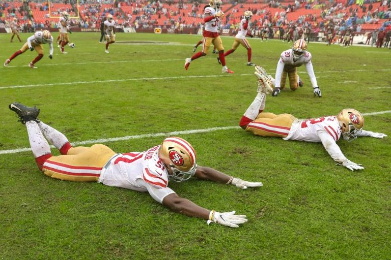 San Francisco linebacker Azeez Al-Shaair, free safety D.J. Reed and 49ers teammates slide on the rain-soaked field after their 9-0 NFL victory over the Washington Redskins (AFP Photo/Patrick Smith)