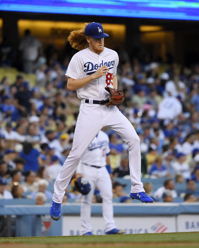 Los Angeles Dodgers starting pitcher Dustin May jumps over the third base line as he goes out for the second inning of the team's baseball game against the San Diego Padres on Friday, Aug. 2, 2019, in Los Angeles. (AP Photo/Mark J. Terrill)