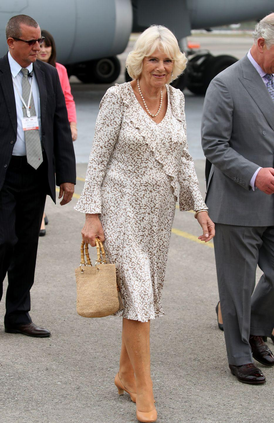 <p>For the royal couple's historic visit to Cuba, Camilla arrived wearing a ruffled brown and white printed dress. She complimented her look with a straw bag, nude heels, and a long-stranded pearl necklace. </p>