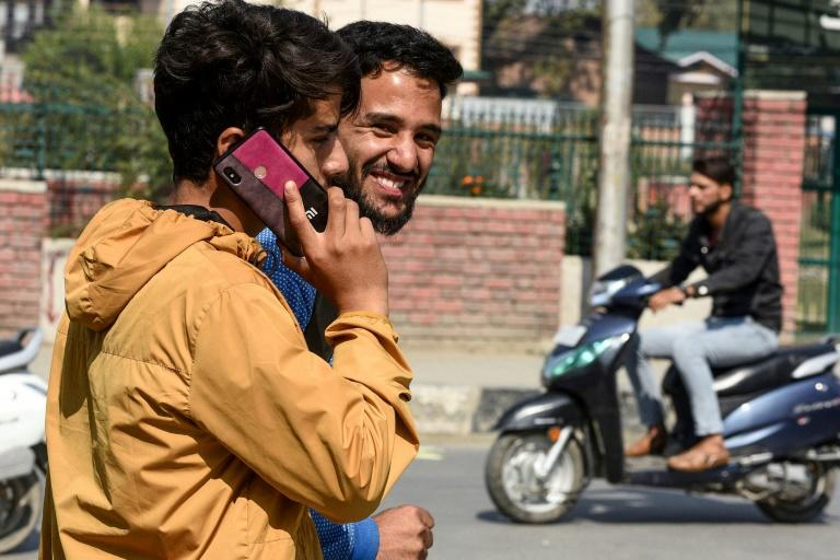 A young man using his phone in Srinagar, in Indian Kashmir, after mobile services were restored