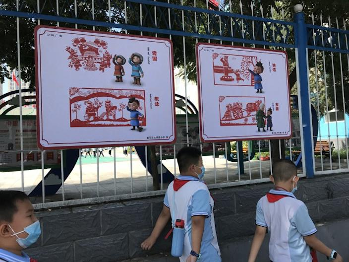 "Elementary school students in Hohhot, the capital of Inner Mongolia, walk past a bilingual sign promoting patriotism and other ""Chinese values"" on Sept. 1, 2020. <span class=""copyright"">(Alice Su / Los Angeles Times)</span>"