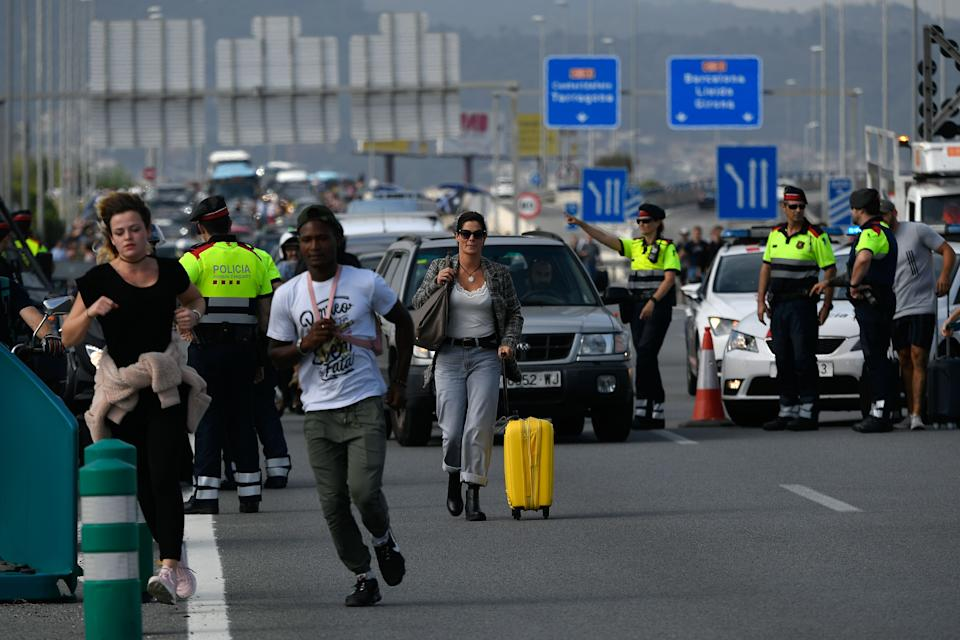 A passengers walks towards El Prat airport as the highway is blocked by Catalan regional police 'Mossos D'Esquadra' officer in Barcelona on October 14, 2019 as thousands of angry protesters took to the streets after Spain's Supreme Court sentenced nine Catalan separatist leaders to between nine and 13 years in jail for sedition over the failed 2017 independence bid. - As the news broke, demonstrators turned out en masse, blocking streets in Barcelona and elsewhere as police braced for what activists said would be a mass response of civil disobedience. (Photo by LLUIS GENE / AFP) (Photo by LLUIS GENE/AFP via Getty Images)