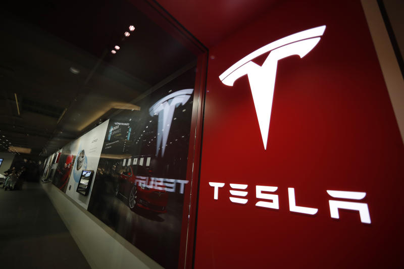 FILE - This Feb. 9, 2019, file photo shows a sign bearing the company logo outside a Tesla store in Cherry Creek Mall in Denver. The U.S. government's road safety agency is sending a special team to Indiana to investigate a fatal crash involving a Tesla electric vehicle. The National Highway Traffic Safety Administration said Wednesday, Jan. 8, 2020, that its team will check the crash scene and inspect the Model 3 vehicle involved in the Dec. 29 crash with a parked firetruck on Interstate 70 near Terre Haute. (AP Photo/David Zalubowski, File)
