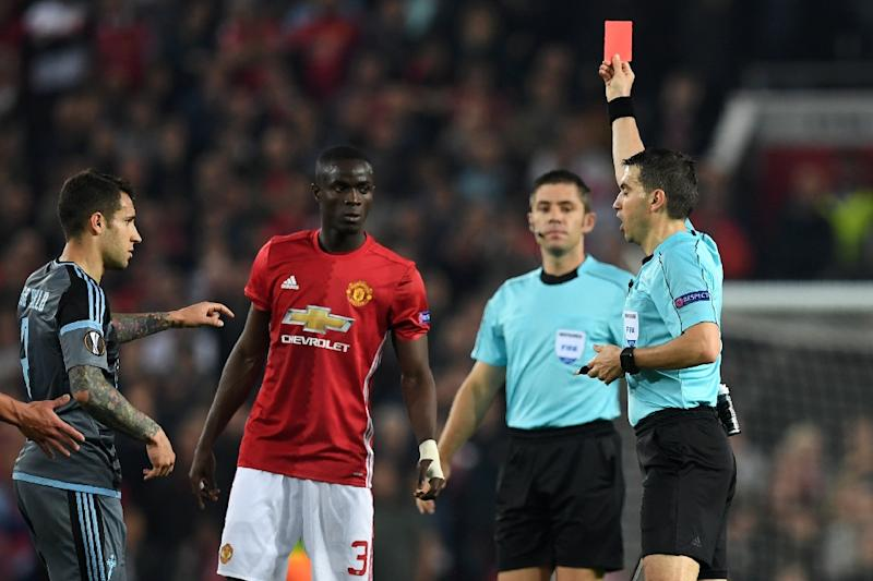 Romanian referee Ovidiu Hategan (R) shows a red card to Manchester United's Eric Bailly (C), after a clash with Celta Vigo players at Old Trafford stadium in Manchester, north-west England, on May 11, 2017 (AFP Photo/Paul ELLIS)