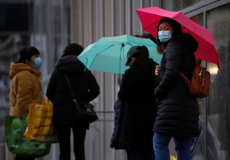 People wearing face masks shelter under umbrellas outside a department store following the outbreak of the coronavirus disease (COVID-19) in Manchester Briain