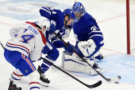 Toronto Maple Leafs defenseman Morgan Rielly (44) moves the puck away from goalie Frederik Andersen (31) as Montreal Canadiens center Nick Suzuki (14) pressures during the first period of an NHL hockey game in Toronto, Wednesday, Jan. 13, 2021. (Frank Gunn/The Canadian Press via AP)