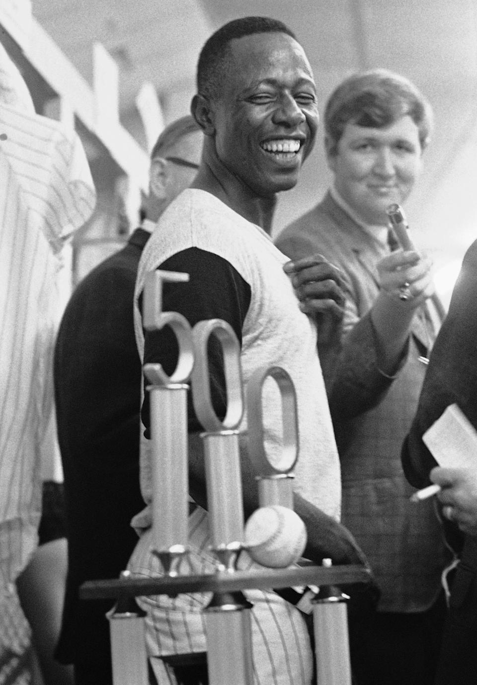 FILE- In this July 14, 1968, file photo, Atlanta Braves' Hank Aaron smiles as he looks at the trophy presented him by Braves President Bill Bartholomay, after Aaron hit his 500th career home run in Atlanta. Hank Aaron, who endured racist threats with stoic dignity during his pursuit of Babe Ruth but went on to break the career home run record in the pre-steroids era, died early Friday, Jan. 22, 2021. He was 86. The Atlanta Braves said Aaron died peacefully in his sleep. No cause of death was given. (AP Photo/Charles Kelly, File)