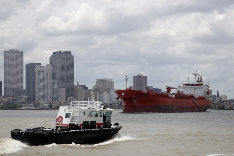 The oil tanker Bow Performer navigates a turn in the Mississippi River in New Orleans, Wednesday, May 13, 2020. Attempts to curb the spread of COVID-19 have visited a kind of triple economic whammy on the state. As oil prices have plummeted, the industry laid off workers. Tourism has dried up, meaning more lost jobs. And one major tourist draw — cuisine built around fin fish, shrimp, oyster and crabs — is also suffering. (AP Photo/Gerald Herbert)