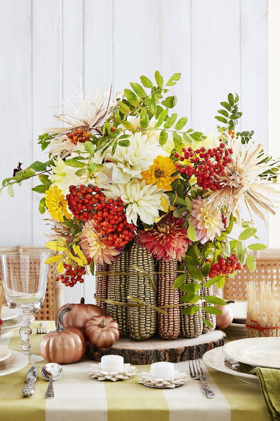 """<p>Give a plain ol' vase some fall flair with this easy idea. Start by coating roughly 14 cobs of dried corn with metallic gold and copper spray paint. Once dry, hot-glue cobs to the perimeter of a 6-inch round vase. Tie it all together with gold raffia. Fill vase with floral foam and add seasonal flowers as desired. (This sampling includes dahlias, zinnias, and mountain ash berries.)</p><p><a class=""""link rapid-noclick-resp"""" href=""""https://www.amazon.com/Iowa-Indian-Corn-Without-husks/dp/B076CVVPV3/ref=sr_1_22?dchild=1&keywords=dried+corn+cobs&qid=1629991146&sr=8-22&tag=syn-yahoo-20&ascsubtag=%5Bartid%7C10050.g.2130%5Bsrc%7Cyahoo-us"""" rel=""""nofollow noopener"""" target=""""_blank"""" data-ylk=""""slk:SHOP DRIED CORN"""">SHOP DRIED CORN</a></p>"""