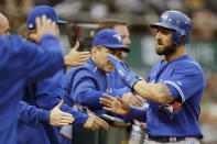 Toronto Blue Jays' Kevin Pillar, right, is congratulated after scoring against the Oakland Athletics in the third inning of a baseball game Tuesday, July 21, 2015, in Oakland, Calif. Pillar scored on a single by Toronto's Jose Reyes. (AP Photo/Ben Margot)