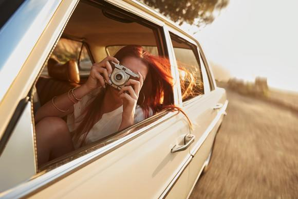 Woman taking a photo on vintage camera (pointed at viewer) on a rural road trip.