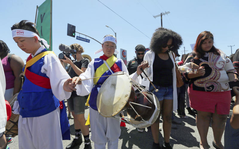 A multiethnic and multicultural crowd hold hands in prayer at the corner of Florence and Normandie, the flash point of the riots that erupted after the 1992 acquittal of four white police officers in the beating of black motorist Rodney King, on the 25th anniversary, in Los Angeles Saturday, April 29, 2017. (AP Photo/Reed Saxon)