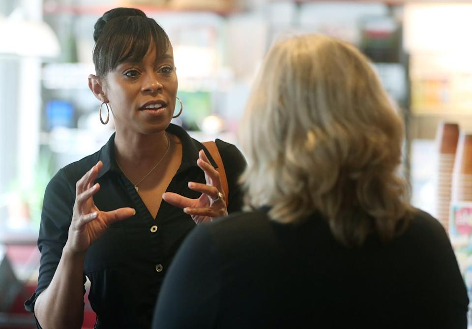 Shontel Brown, candidate for the OH-11 Congressional District, talks with Nancy Holland, Akron city council ward 1,   at Angel Falls Coffee shop during a campaign stop in Akron on Wednesday July 14, 2021.