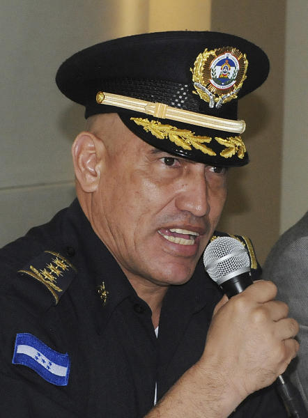 "In this May 22, 2012 photo, officer on Juan Carlos Bonilla Valladares, known as ""El Tigre"" or ""The Tiger"" speaks to the press after he was sworn-in as Honduras' new Chief of Police in Tegucigalpa, Honduras. Bonilla Valladares, the new chief chosen to clean up a Honduran national police force tarred with allegations of corruption and involvement in murders was accused by the department's internal affairs investigators of running a death squad when he was a top regional police official. (AP Photo/Fernando Antonio)"