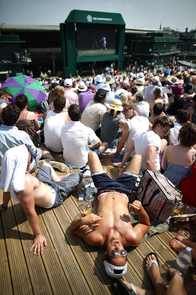 LONDON, ENGLAND - JULY 07: Spectators rest in the sun as they watch a giant TV showing Britain's Andy Murray play Novak Djokovic of Sebia in the gentleman's singles final at the Wimbledon Lawn Tennis Championships at the All England Lawn Tennis and Croquet Club at Wimbledon on July 7, 2013 in London, England. (Photo by Peter Macdiarmid/Getty Images)