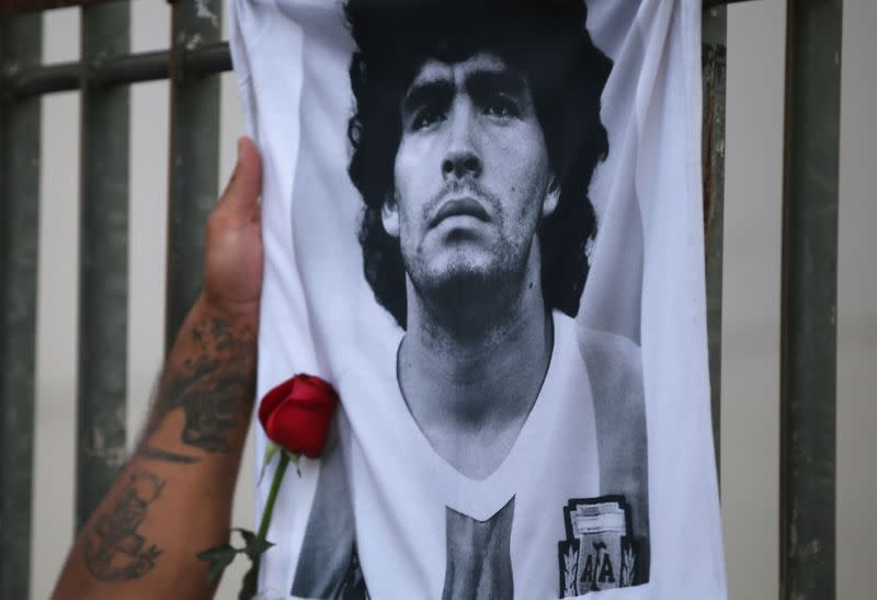 A rose is placed next to a banner of Argentine soccer great Diego Maradona as fans gather to mourn his death, at the Obelisk of Buenos Aires