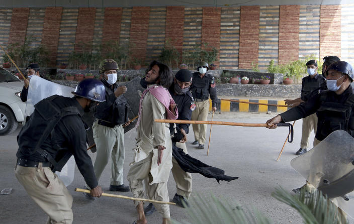 Police officers hit a supporter of Tehreek-e-Labiak Pakistan, a radical Islamist political party, before detain him at a protest against the arrest of their party leader, Saad Rizvi, in Peshawar, Pakistan, Tuesday, April 13, 2021. Two demonstrators and a policeman were killed Tuesday in violent clashes between Islamists and police in Pakistan, hours after authorities arrested Rizvi in the eastern city of Lahore, a senior official and local media reported. (AP Photo/Muhammad Sajjad)