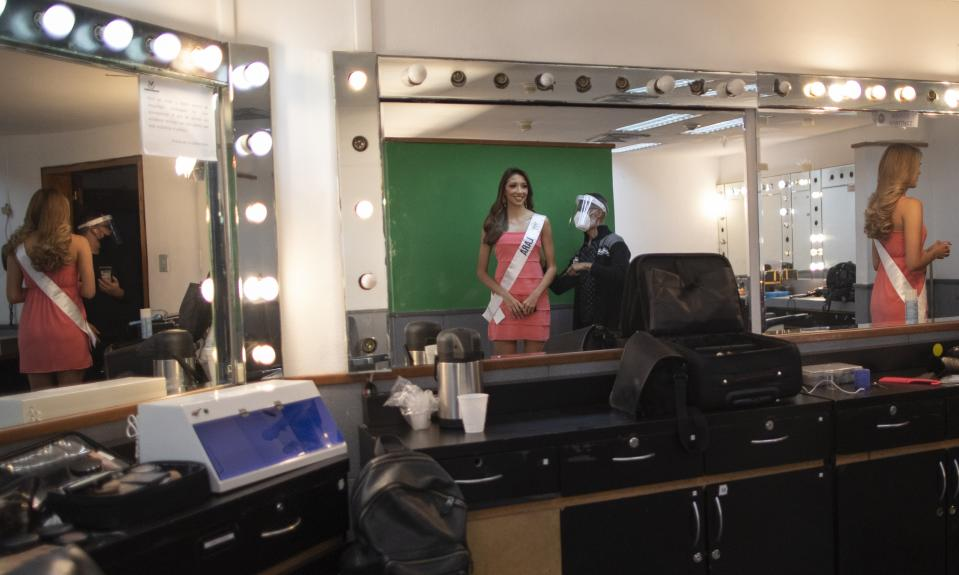 Lara state beauty pageant contestant Jhosskaren Carrizo looks into a mirror in a Venevision television station dressing room, before a meeting with judges, in Caracas, Venezuela, Friday, Sept. 18, 2020. Quarantine rules and social distancing has forced the contestants to train at home and online with limited access to the venue itself where strict measures are in place. The Miss Venezuela beauty pageant is due to take place on Sept. 24. (AP Photo/Ariana Cubillos)