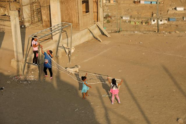 """Women and children tie a volleyball net to a goal post before a volleyball match at a makeshift soccer field in Nueva Union shantytown in Villa Maria del Triunfo district of Lima, Peru, April 25, 2018. REUTERS/Mariana Bazo SEARCH """"NUEVA SOCCER"""" FOR THIS STORY. SEARCH """"WIDER IMAGE"""" FOR ALL STORIES."""