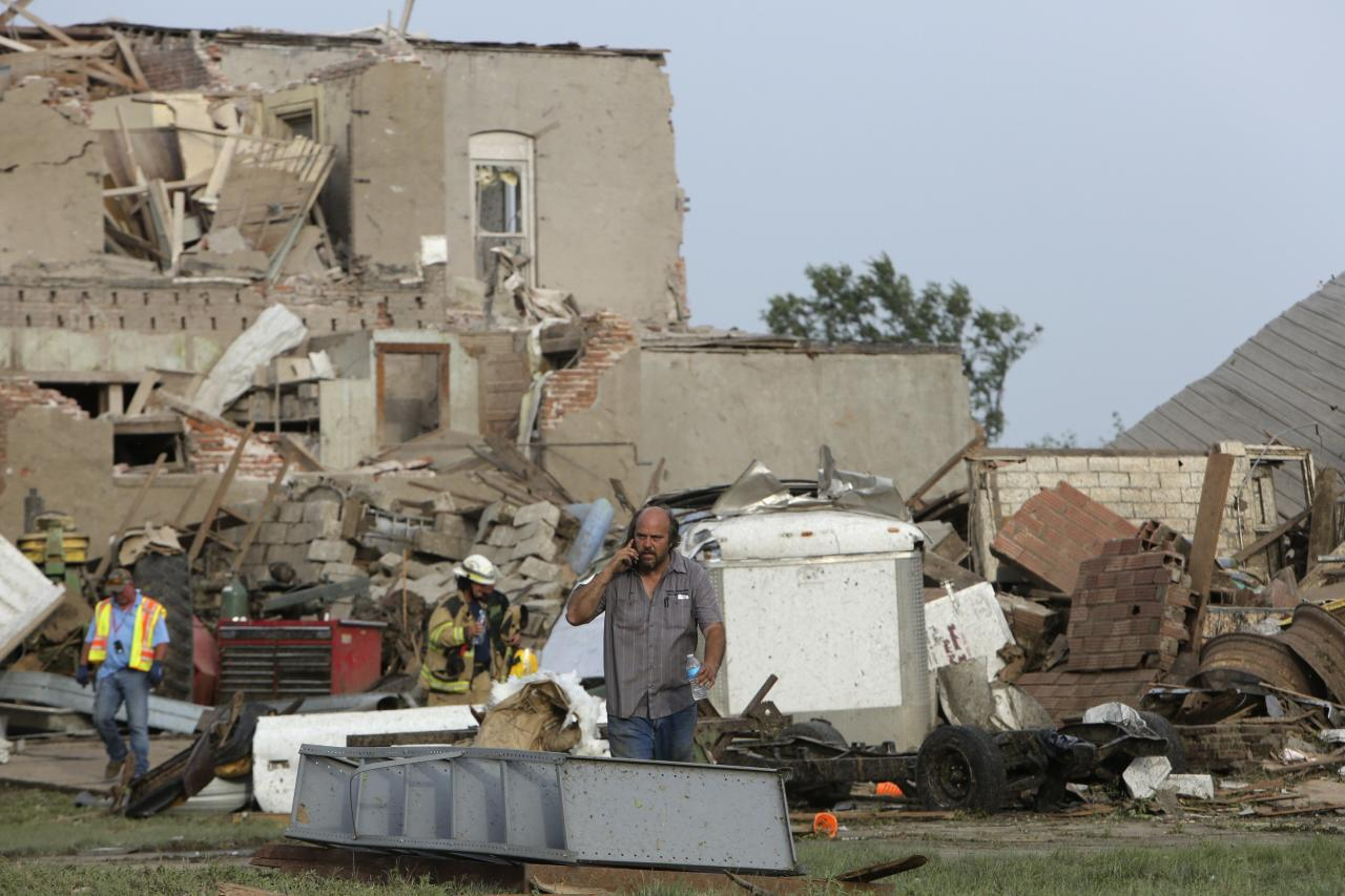 A man talks on the phone in front of tornado-damaged buildings in Pilger, Nebraska June 16, 2014. A swarm of tornadoes, some appearing two at a time, struck several farming communities in northeastern Nebraska on Monday, killing at least one person and injuring 16 in the tiny town of Pilger obliterated by a direct hit, officials said. REUTERS/Lane Hickenbottom (UNITED STATES - Tags: ENVIRONMENT DISASTER TPX IMAGES OF THE DAY)