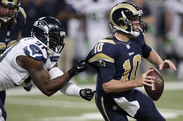 Seattle Seahawks defensive end Chris Clemons (91) grabs on to St. Louis Rams quarterback Kellen Clemens' jersey during the second half of an NFL football game, Monday, Oct. 28, 2013, in St. Louis. (AP Photo/Tom Gannam)
