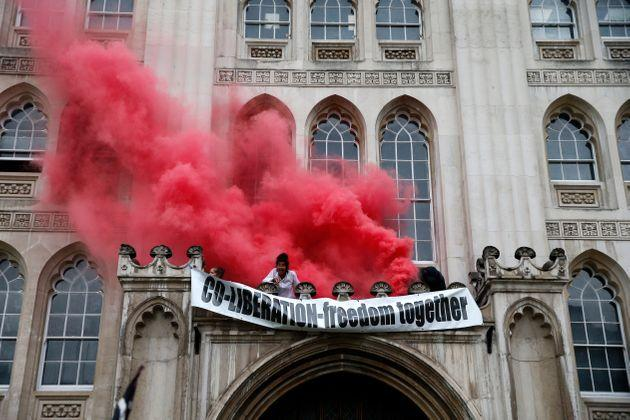 Protesters from Extinction Rebellion light a flare and unfurl a banner from the Guildhall on August 22, 2021 in London, England (Photo: Hollie Adams via Getty Images)