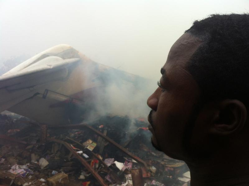 A man looks at the wreckage of a passenger plane that crashed into buildings in a neighborhood just north of Murtala Muhammed International Airport, in Lagos, Nigeria, Sunday, June 3, 2012. The passenger plane carrying more than 150 people crashed in Nigeria's largest city on Sunday, government officials said. The Lagos state government said in a statement that 153 people were on the Dana Air flight Sunday. (AP Photo/Jon Gambrell)
