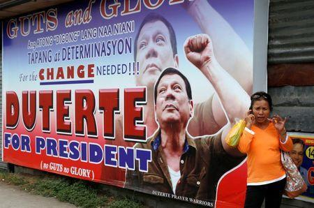 """A resident talks on her mobile phone beside a huge election campaign poster of leading presidential candidate Rodrigo """"Digong"""" Duterte in Davao city, southern Philippines, May 11, 2016. REUTERS/Erik De Castro"""