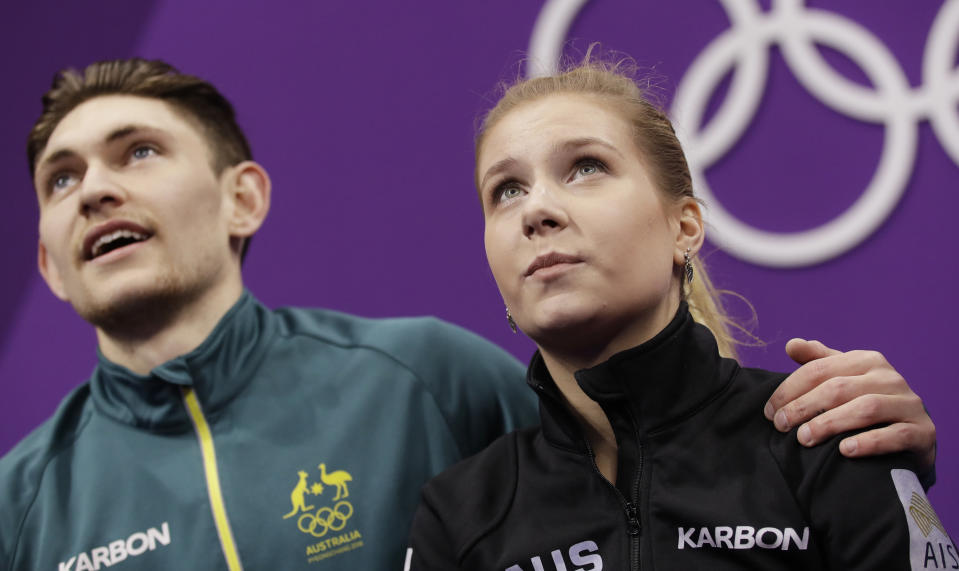 Ekaterina Alexandrovskaya and Harley Windsor of Australia watch as their scores are posted at the 2018 Winter Olympics.