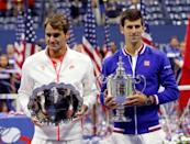 Roger Federer (L) holds his runner-up prize as Novak Djokovic holds the U.S. Open trophy after Djokovic won their men's singles final match at the U.S. Open Championships tennis tournament in New York, September 13, 2015. REUTERS/Mike Segar