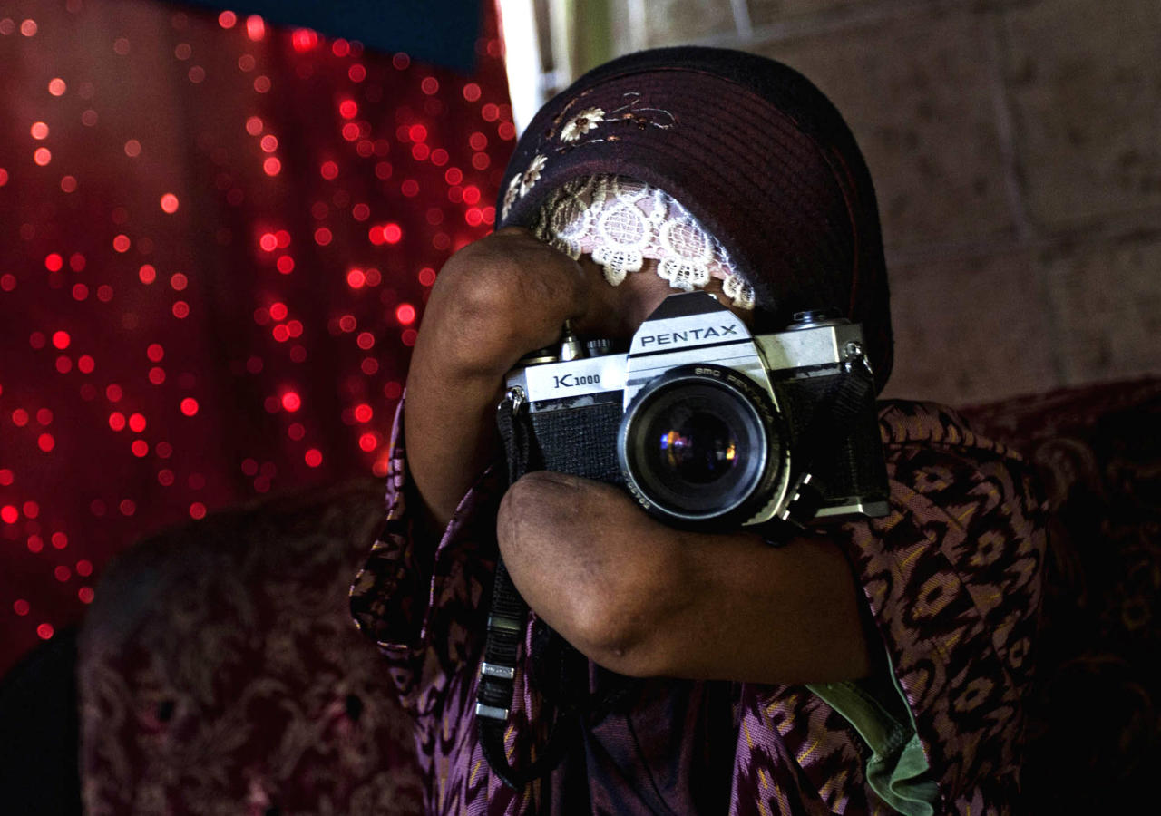 Armless professional photographer Rusidah, 44, takes a photograph as she carries out camera maintenance on March 13, 2012 in Purworejo, Indonesia. (Photo by Ulet Ifansasti/Getty Images)