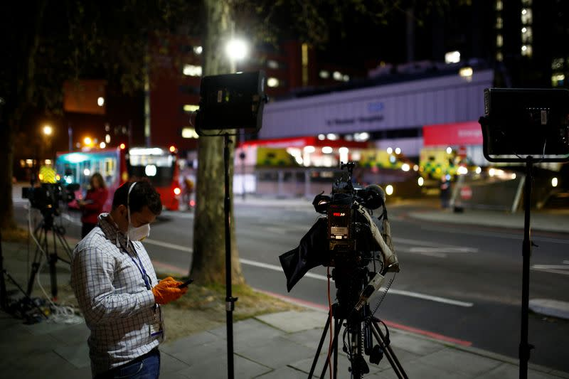 A journalist wearing a face mask is seen outside of the St Thomas' Hospital after British Prime Minister Boris Johnson was moved to intensive care