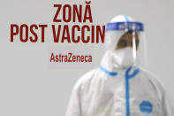 A man wearing a protective outfit stands in an area where people who have just been injected with the AstraZeneca vaccine have to wait for 15 minutes to make sure they don't develop immediate side effects at a vaccination center in Bucharest, Romania, Tuesday, March 23, 2021. AstraZeneca's repeated missteps in reporting vaccine data coupled with a blood clot scare could do lasting damage to the credibility of a shot that is the linchpin in the global strategy to stop the coronavirus pandemic, potentially even undermining vaccine confidence more broadly, experts say.(AP Photo/Vadim Ghirda)
