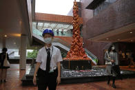 """A security guard stands in front of the """"Pillar of Shame"""" statue, a memorial for those killed in the 1989 Tiananmen crackdown, at the University of Hong Kong, Wednesday, Oct. 13, 2021. Danish artist Jens Galschioet is seeking to get back his sculpture in Hong Kong memorializing the victims of China's 1989 Tiananmen Square crackdown as a deadline loomed for its removal Wednesday. (AP Photo/Kin Cheung)"""