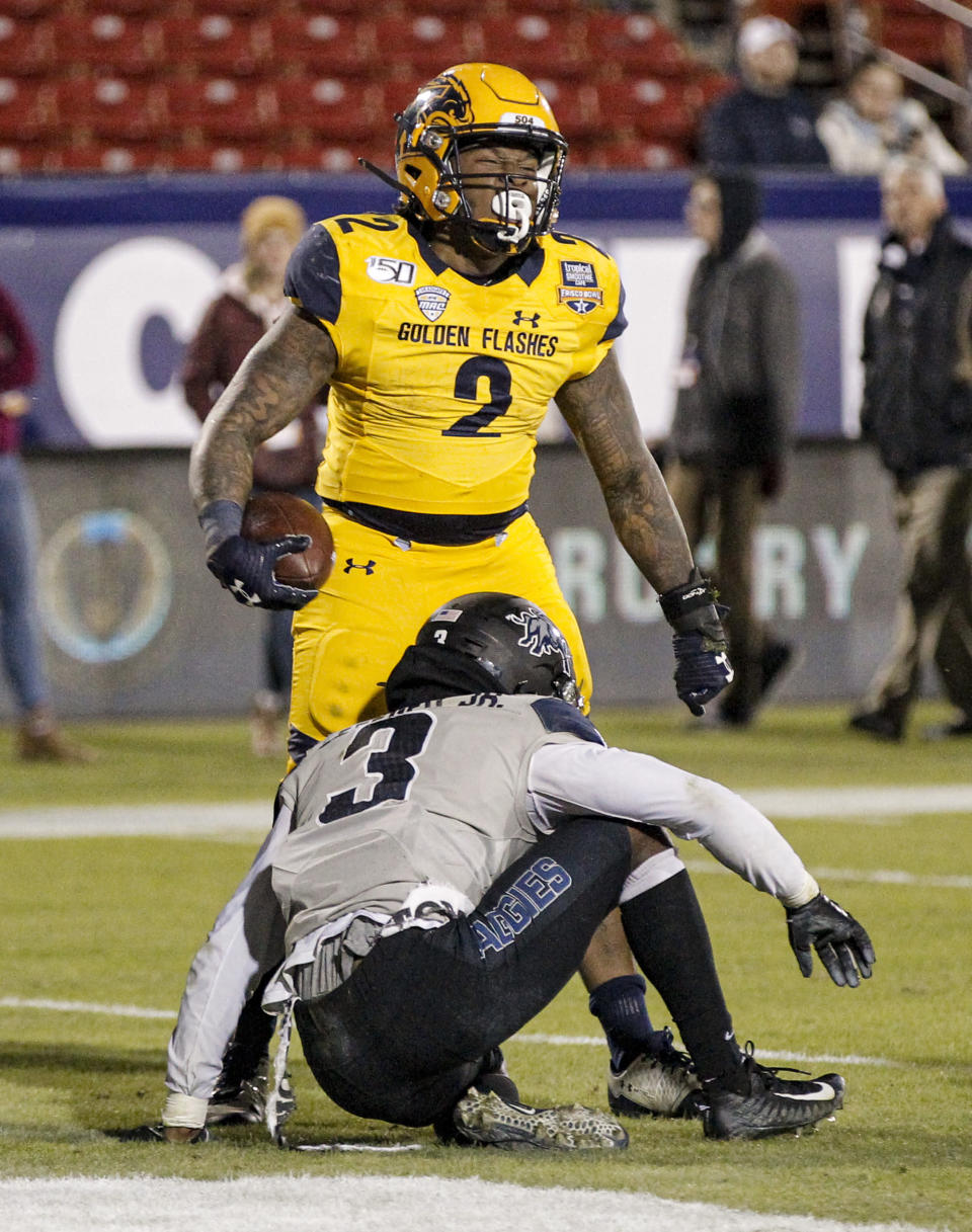 Kent State running back Will Matthews (2) celebrates his touchdown as Utah State safety Troy Lefeged Jr. (3) gets up during the second half of the Frisco Bowl NCAA college football game Friday, Dec. 20, 2019, in Frisco, Texas. Kent State won 51-41. (AP Photo/Brandon Wade)