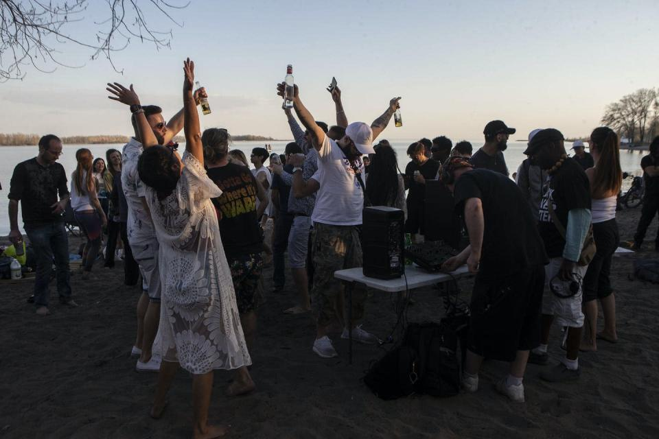 People dancing and drinking on a beach at sunset.
