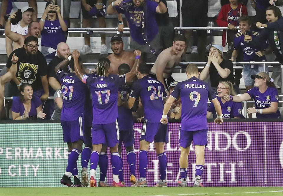 Orlando players celebrate with Benji Michel (19) after he scored a goal during a MSL soccer match in Orlando, Fla., on Tuesday, June 22, 2021. (Stephen M. Dowell /Orlando Sentinel via AP)