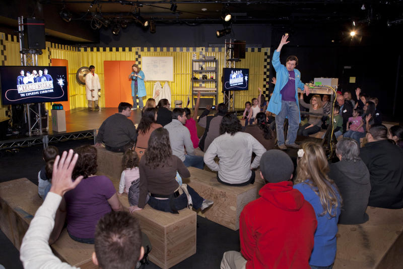 """In this March 10, 2012 photo provided by the Museum of Science and Industry, friends and family of museum staff listen to Brett Nicholas, manager of Guest Programs at the Museum of Science and Industry in Chicago asking a question at the Live Demonstration Stage during setup for the show """"MythBusters: The Explosive Exhibition,"""" modeled after the Discovery Channel television show """"Mythbusters"""" The exhibit opens Thursday, March 15 and runs through Sept. 3. The planned national tour that will include stops at several other U.S. cities. (AP Photo/Museum of Science and Industry, J.B. Spector)"""