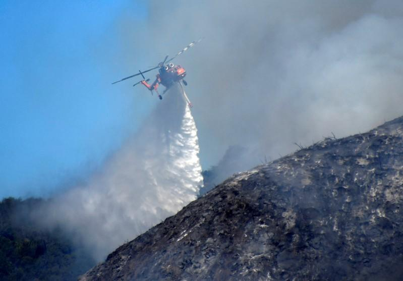 Firefighters battle a blaze from the air that was threatening homes in the Pacific Palisades community of Los Angeles