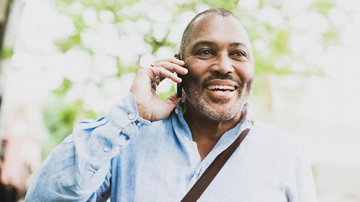 A cheerful African American man in his early 60's smiles, standing outdoors and looking relaxed, confident, and content as he talks on his smart phone.