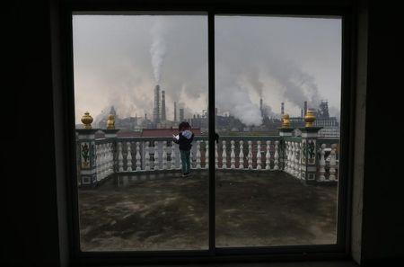 A girl reads a book on her balcony as smoke rises from chimneys of a steel plant, on a hazy day in Quzhou