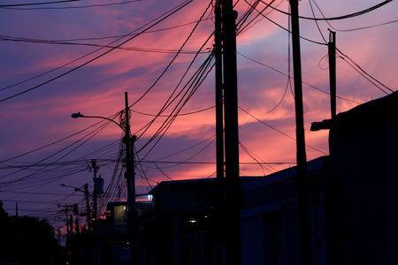 Electrical posts and power lines are seen at sunset during a blackout in Maracaibo, Venezuela July 26, 2018. REUTERS/Marco Bello