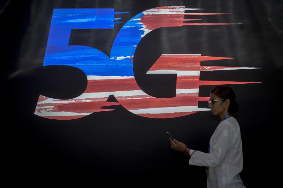 A woman uses a smartphone as she walks pass a 5G logo during the launch of the 5G Showcase in Putrajaya April 18, 2019. — Picture by Mukhriz Hazim