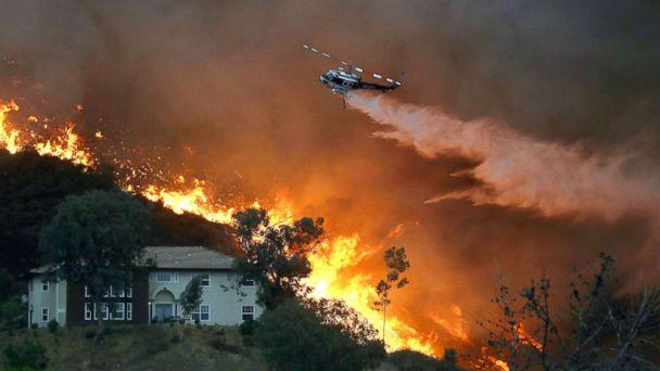 PHOTO: A firefighting helicopter makes a water drop as the Holy Fire burns near homes, Aug. 9, 2018, in Lake Elsinore, Calif. (Mario Tama/Getty Images)