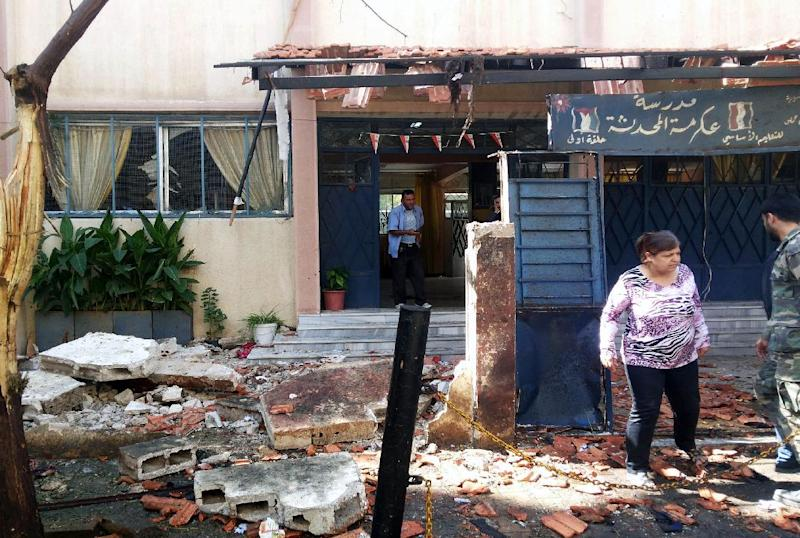 Syrians inspect the scene of a car bomb explosion outside the Akrameh al-Makhzumi school in Homs, on October 1, 2014